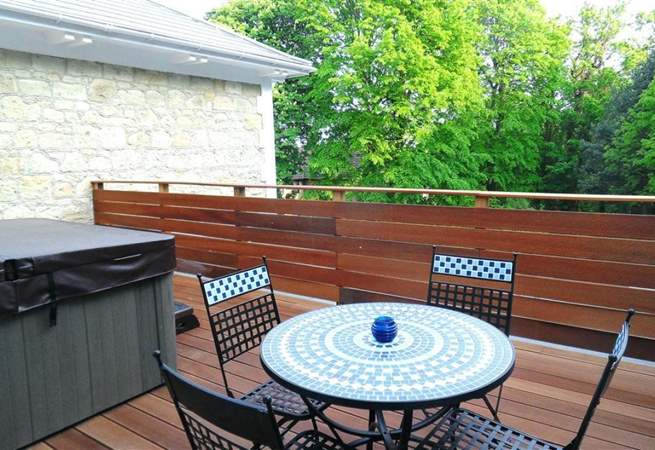 Private decked patio with hot tub and sun loungers.