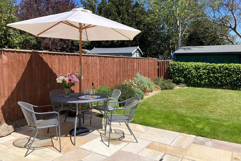 A charming enclosed garden with patio furniture and sun loungers