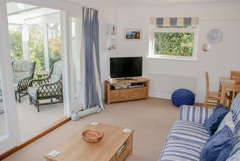 Comfortable sitting-room with doors into the sunny conservatory, a peaceful place to sit back and relax.