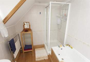 Family bathroom with walk in shower cubicle and bath tub.