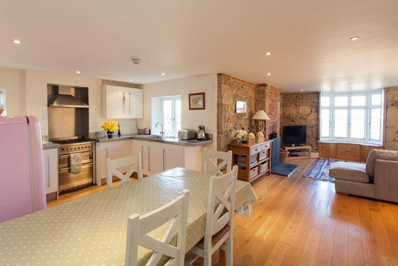 Large open plan kitchen, dining and living area with original stone walls