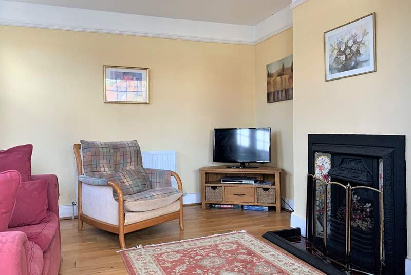 The sitting-room is a comfortable haven with a cosy fireplace.