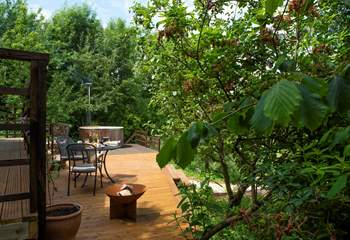 The large decked-area has a fire pit and charcoal barbecue.