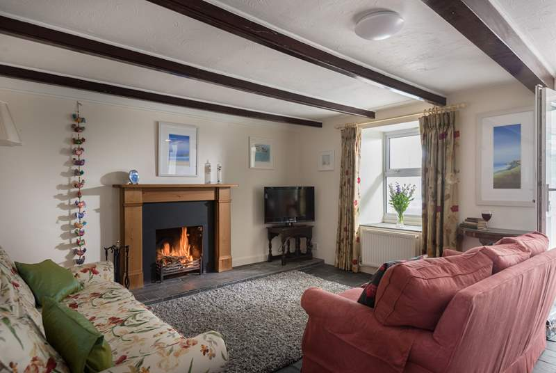 The cosy sitting-room with two sofas around the open fire.