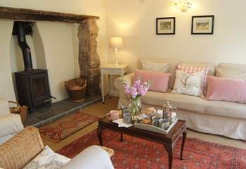 The wonderful welcoming  sitting-room has an inglenook fireplace and a wood-burning stove.