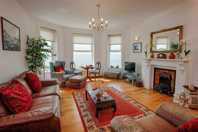 Lovely light and spacious living-room with plenty of comfortable seating to relax in.