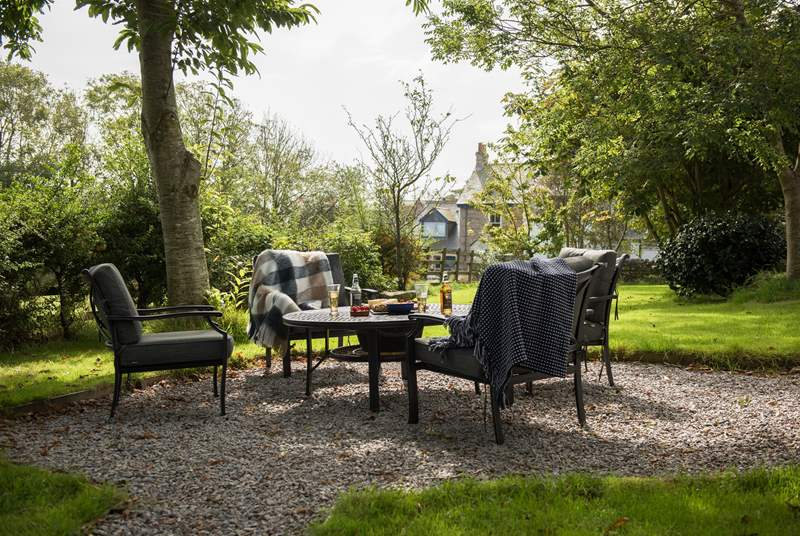The private garden looks out over a meadow, with a fire-pit and comfortable, cushioned seating...