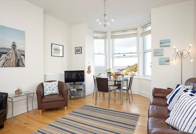 The open plan space has high ceilings, a wooden floor and a large bay window with extensive sea view!