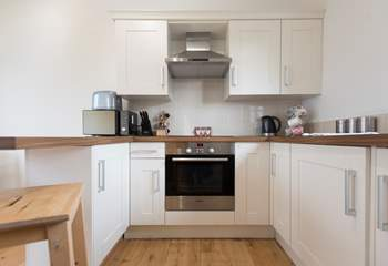 The kitchen is complete with an induction hob, and is compact, light and airy.