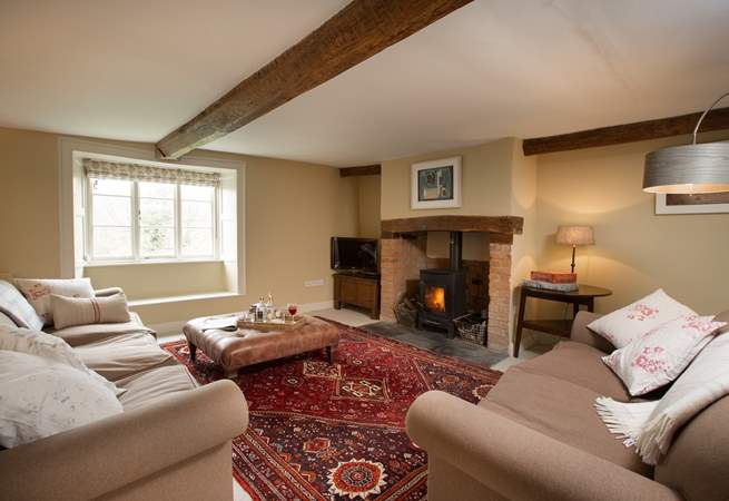 This is the sitting-room with a wood-burning stove, deep comfortable sofas and a lovely warm atmosphere.