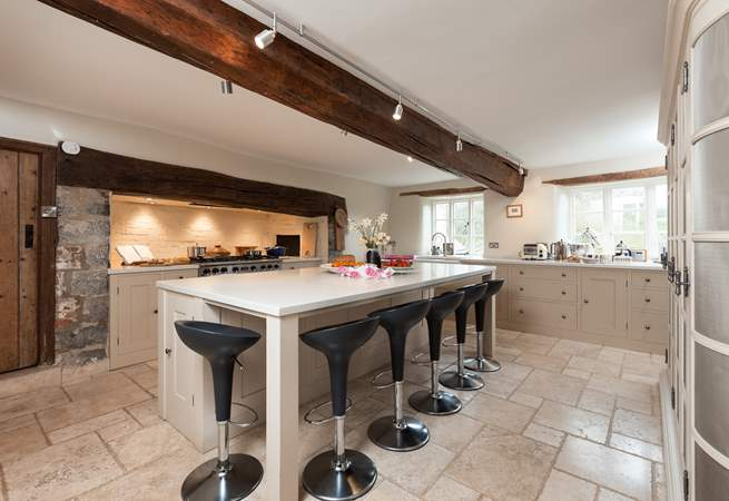 The farmhouse has a stunning contemporary kitchen with a range cooker, a huge sociable island and gorgeous stone flooring.