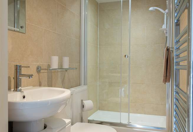 The fully tiled shower-room has a large cubicle.