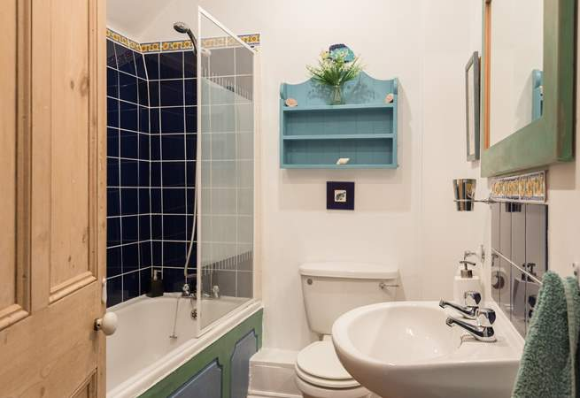 This bathroom has a bath with an overhead shower.