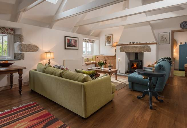 Cosy sitting-room with comfy sofas and wood-burner. There is a good selection of books to read and games to play.