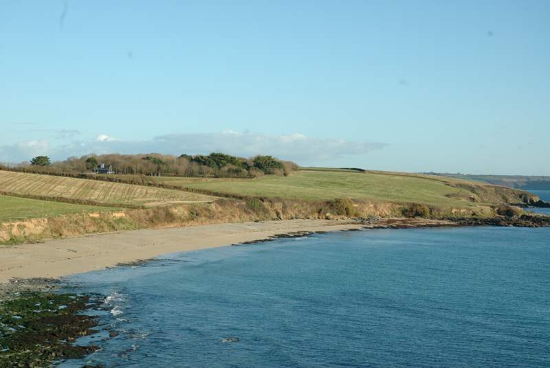 Looking at Towan Beach from Killigerran Headland with Rosteague Farmhouse nestling in the trees on the left.
