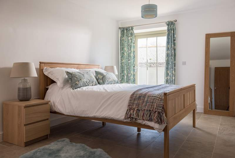 The master bedroom is spacious and light and has a comfy king-size bed dressed with lovely linens.