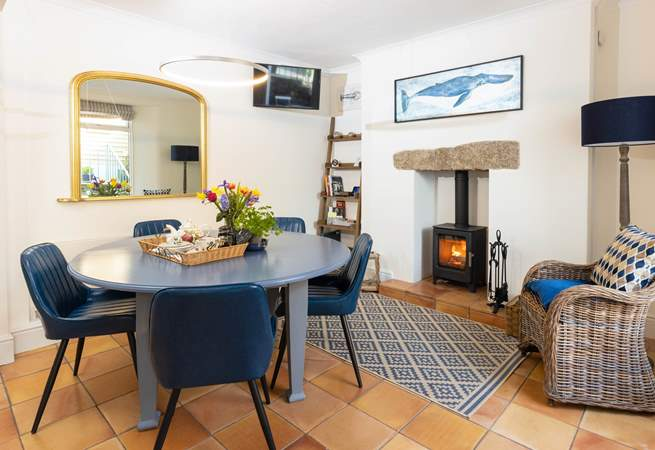 The dining area has comfy chairs,  enjoy sitting around the table with the cosy wood burner glowing.