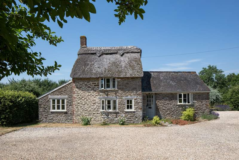 This listed, thatched cottage has a private south-facing garden behind the cottage, the owner's house is to the right.