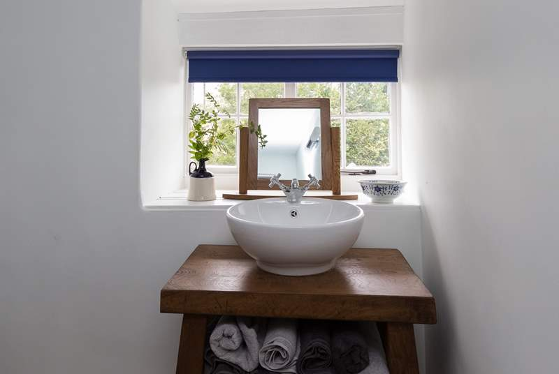 There is a stylish bespoke basin surround.