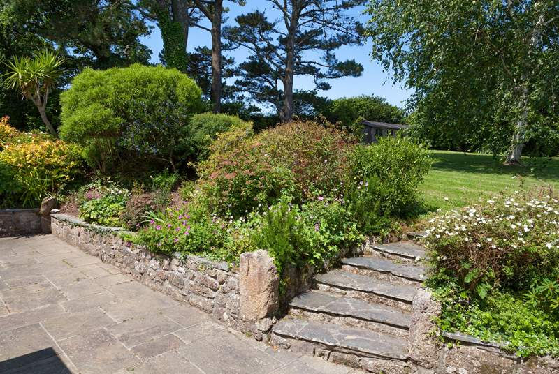 The borders are jam packed with colourful shrubs and the mature trees provide shade when the sun is beating down.