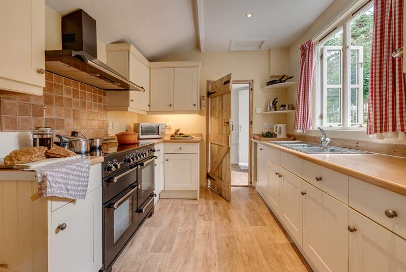 The kitchen/dining-room has a large range cooker. Beyond the kitchen is a utility-room and the back door to the garden.