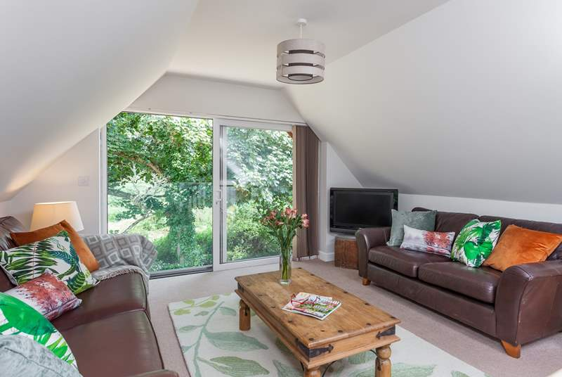 The open plan sitting-room is richly styled in greens and browns to complement the outside.