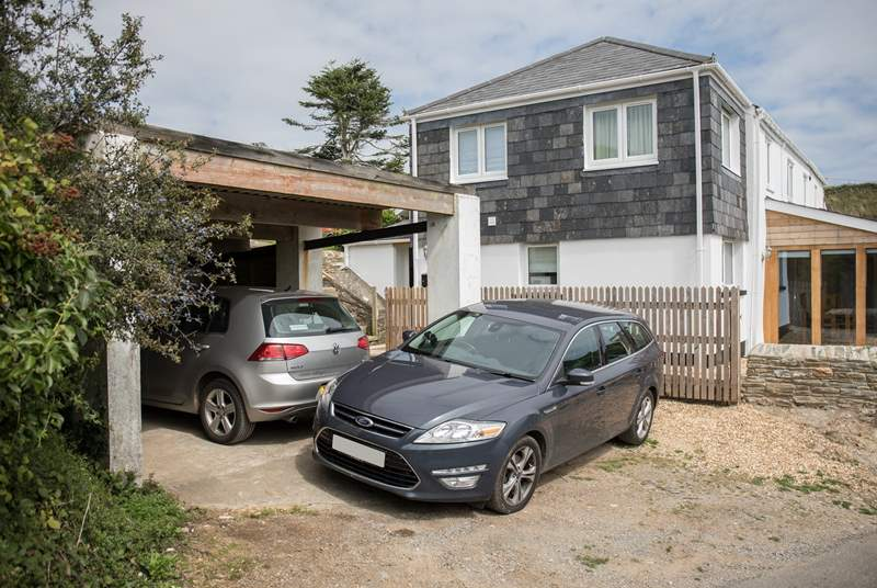 There is parking for two cars. However, with some very experienced parking skills, you could squeeze two small cars into the carport, leaving you space for a third in front.