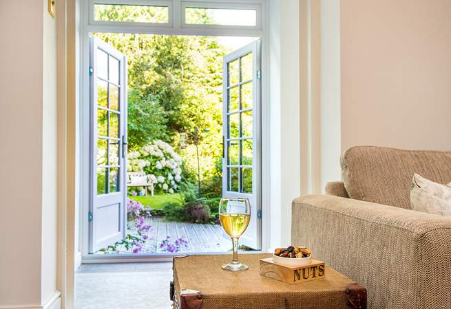 Double doors lead out from the sitting-room through the sun-room to the garden.