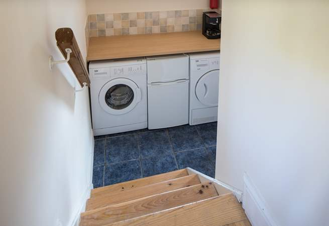The utility-room houses the washing machine, tumble-drier and extra freezer.