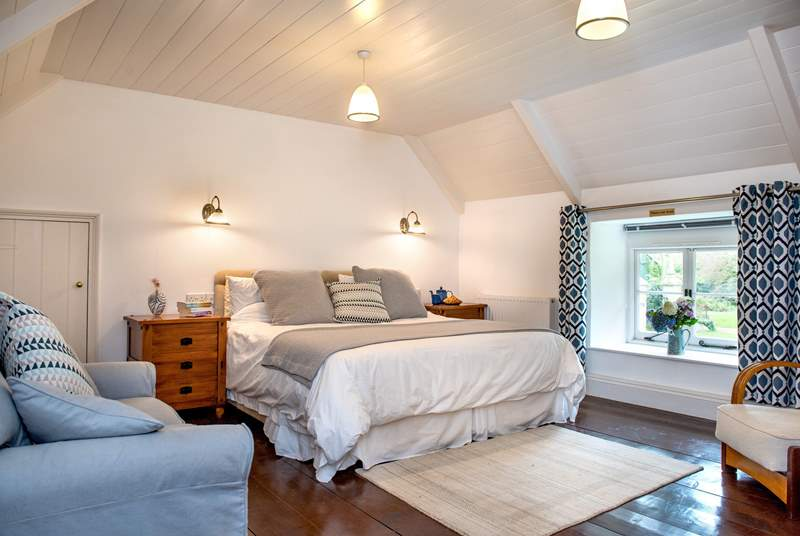 The large bedroom has a super-king bed and overlooks the cottage's pretty front garden.