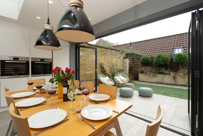 The bi-fold glass wall folds easily back so that the enclosed garden becomes part of the fabulous living space.