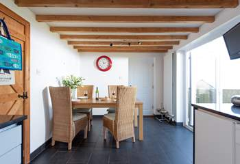 The dining-area has doors that lead out to the enclosed garden with its decked terrace and sea views.