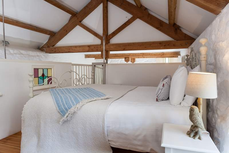 The bedroom retains much of the character of the original barn, with lovely stone walls and exposed beams.