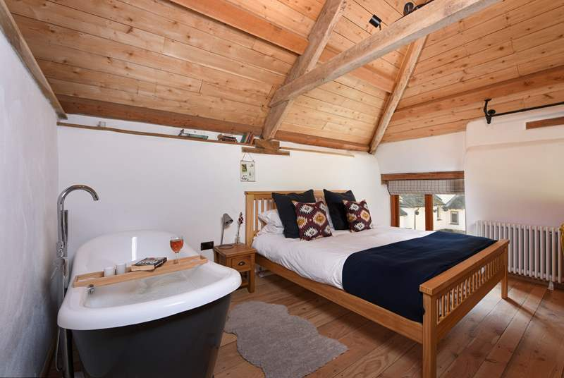 The bedroom is on a mezzanine level and boasts a gorgeous roll-top bath.