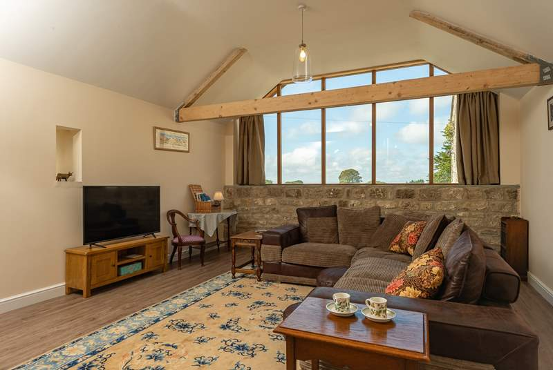 The L-shaped sofa is deep and comfortable and the large windows at the end of this open space include a glimpse of Glastonbury Tor.