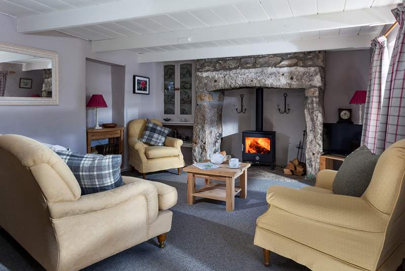 Up a step into the cosy sitting-room with wood-burning stove.