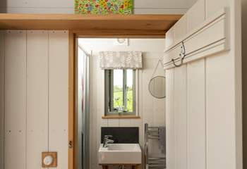 The shower-room sits at the opposite end of the hut to the bed.