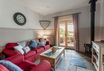 The comfortable living space with wood-burning stove and French doors opening onto the private decking area.