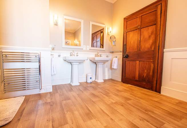 Family bathroom with double wash-basins and a roll-top bath.