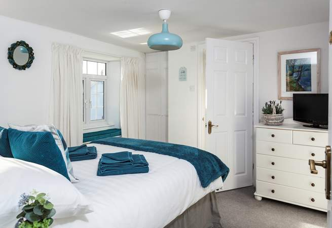 This is the double bedroom, with lovely linens and a window seat to curl up on.