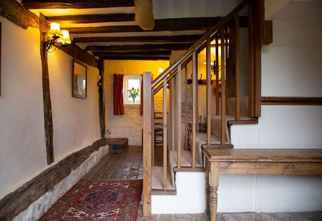 Entrance hall with brick floor and exposed beams.