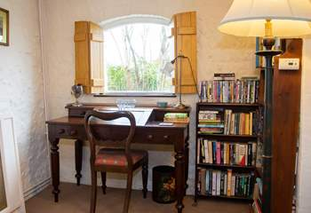 Writing desk and plenty of books for all ages to keep you entertained.