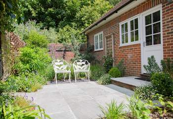 Step outside from the kitchen to an additional enclosed garden with seating for two.