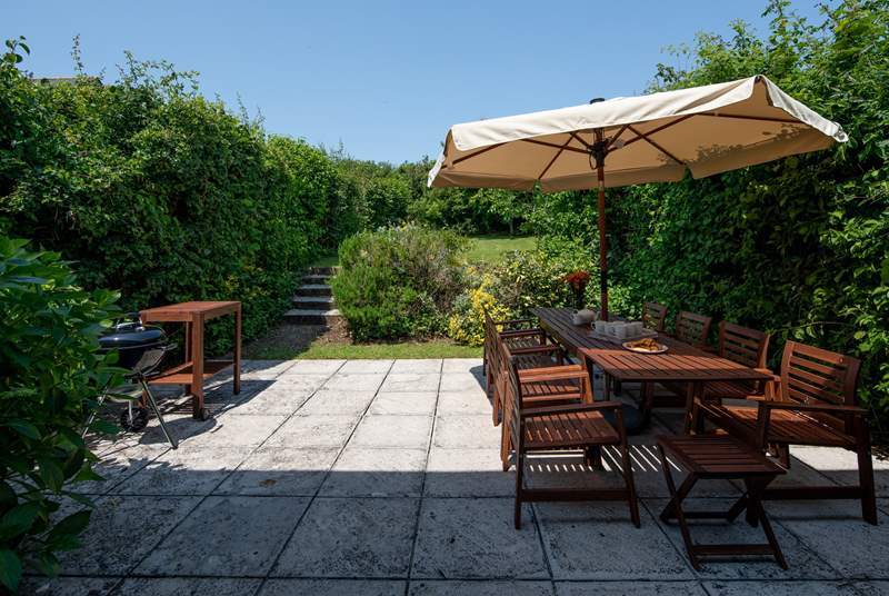 Step out of the house onto this fabulous patio and large garden which stretches out beyond.