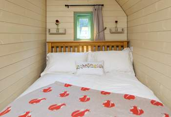 The comfortable double bed looks out to the double doors to the view beyond.