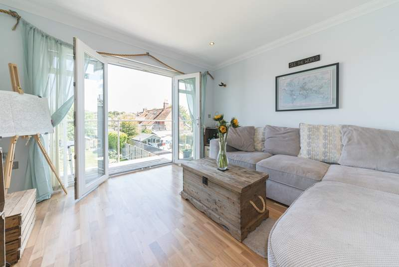Light and airy, the open plan living-room with kitchen, dining area and balcony.