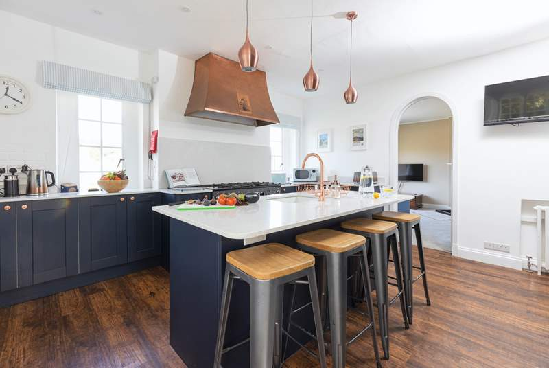 The modern kitchen with the original cooker hood. The snug leads off the kitchen.