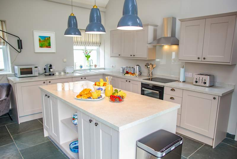 The modern bright kitchen sits within the open plan central living area.