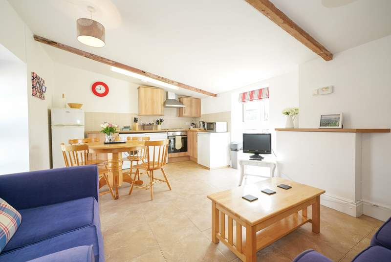 The open plan living-room with kitchen and dining areas is light and airy.
