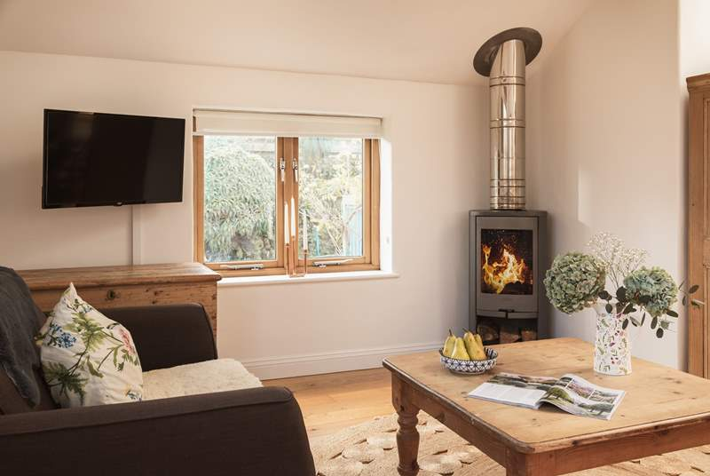 The lovely wood-burner complements the living area.